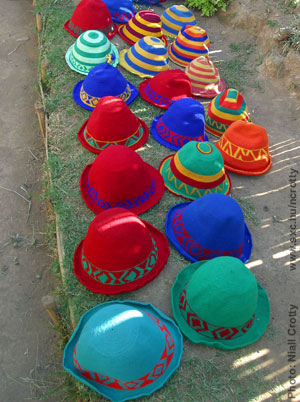 Photo by Niall Crotty of many colourful hats on a bench. 